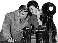Film star ANTHONY STEEL and film editor ANNE COATES looking at film on a Movieola viewer